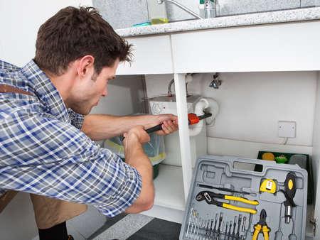 plomeria: Fontanero joven que trabaja con la llave de tubo en la cocina