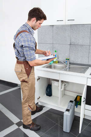Handsome Young Plumber Writing On Clipboard With Pen In Kitchen Room photo