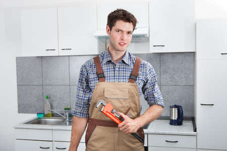 Happy Young Plumber Holding Pipe Wrench In Kitchen Room photo