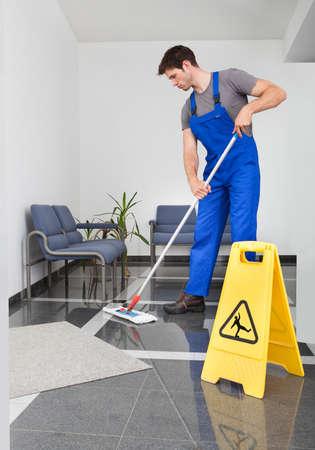 사무실에서 걸레로 바닥을 청소하는 젊은 남자의 초상화 스톡 콘텐츠