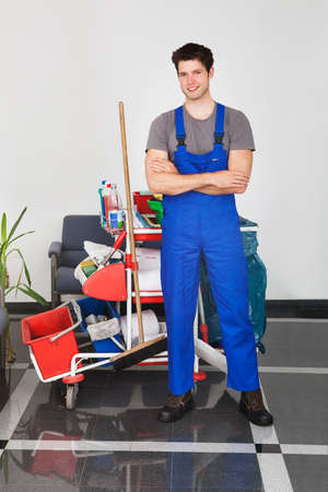 cleaning an office: Portrait Of Young Happy Man Standing With Cleaning Equipment In Office Stock Photo