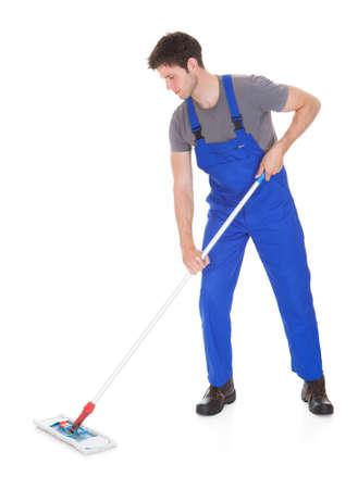 pulizia pavimenti: Giovane uomo in uniforme blu pulizia pavimento su sfondo bianco
