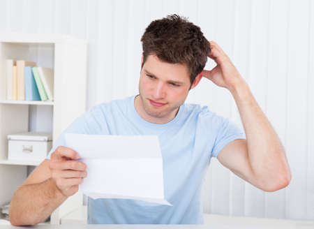 Contemplated Young Man Reading Paper Holding In Hands Stock Photo - 23361924