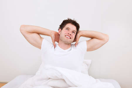 Young Happy Man Raising Arm Sitting On Bed photo