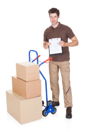 Young Delivery Man Holding Clip Board Standing With Stack Of Boxes Stock Photo - 23361938