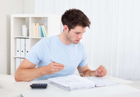 Young Man Calculating His Finance Expenses At Home photo