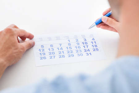 Close-up Of Man Holding Pen And Looking At Date On Calendar photo