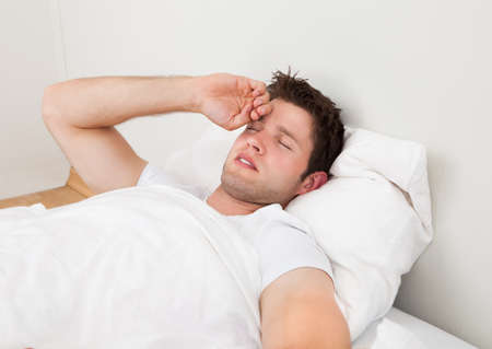 Young Man Suffering From Headache Lying On Bed photo