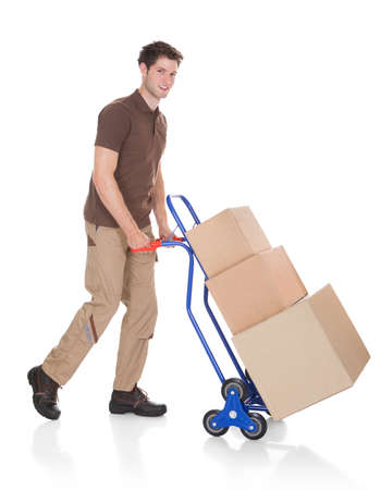 Young Happy Delivery Man Carrying Boxes On A Hand Truck photo