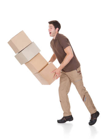Young Delivery Man Dropping Stack Of Cardboard Boxes photo