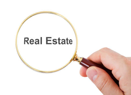 Close-up Of Hand Showing Real Estate Word Through Magnifying Glass Over White Background Stock Photo - 23361975