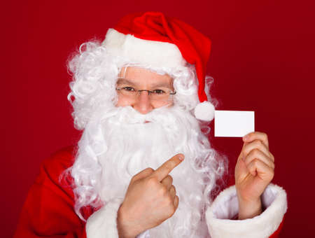 Portrait of a santa holding blank visiting card over red background photo