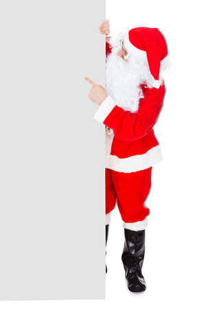 holding a christmas ornament: Portrait of a santa holding blank placard over white background