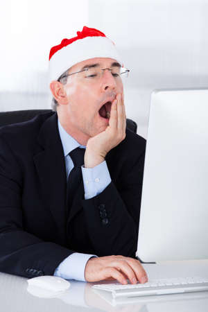 Mature Businessman With Santa Hat Yawning While Working On Computer photo