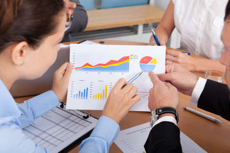 Close-up Of Businesspeople Analyzing Graph Together In Office photo