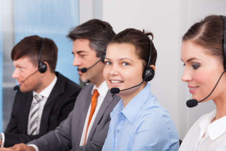 Call center operator sitting in row working at office photo
