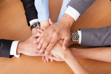 High Angle View Of Businesspeople Stacking Hands Over Each Other photo