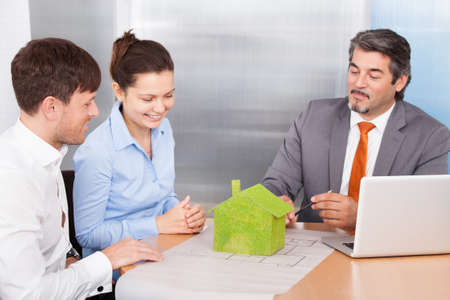 Happy Young Couple Discussing With Mature Consultant photo