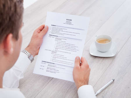 resume: Close-up Of Businessman Reading Resume With Tea Cup On Desk Stock Photo