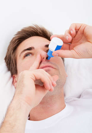 inhale: Close-up Of Young Man Using Nasal Spray