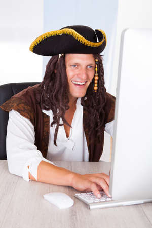 Portrait Of A Happy Young Pirate Using Computer photo