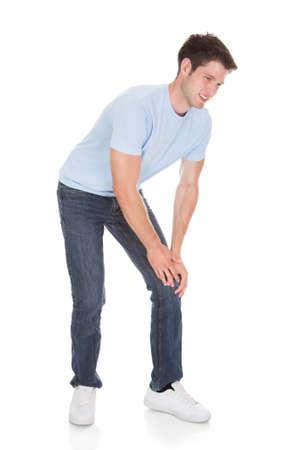 dolor de rodilla: Hombre joven que sufre de dolor de rodilla aislado en fondo blanco Foto de archivo
