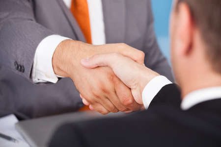Handshake business: Two Business Partner Shaking Hands In Front Of Colleagues Stock Photo