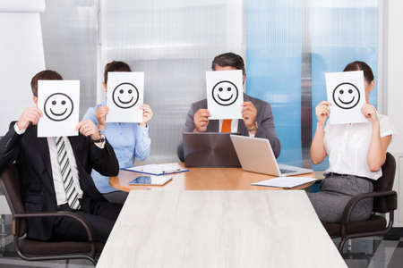 jury: Group Of Businesspeople Sitting In A Conference Room Holding Smiley Icon Stock Photo