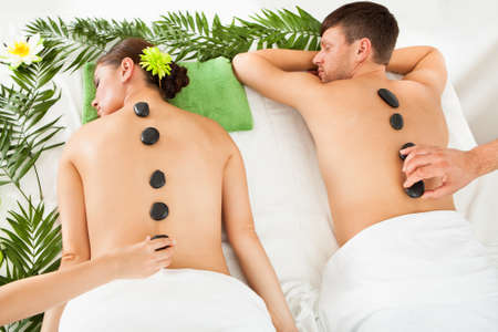 Couple Relaxing In A Spa Getting Lastone Therapy Stock Photo - 23490760