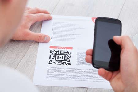 capture: Close-up Of Hand Holding Mobile Scanning Bar Code