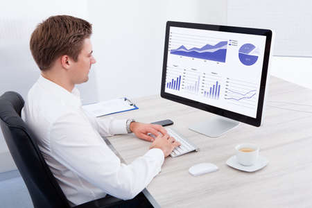 typing on computer: Portrait Of Young Businessman Using Computer At Desk Stock Photo