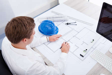 civil engineer: Portrait Of A Young Architect Drawing Plan On Blueprint Stock Photo
