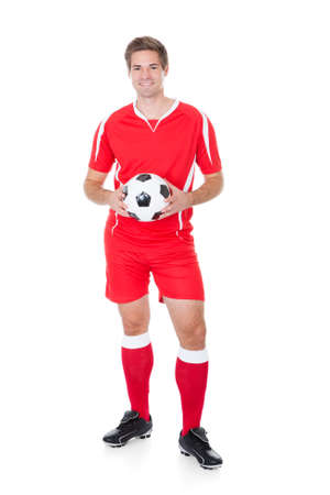 Portrait Of A Soccer Player Holding Football On White Background photo
