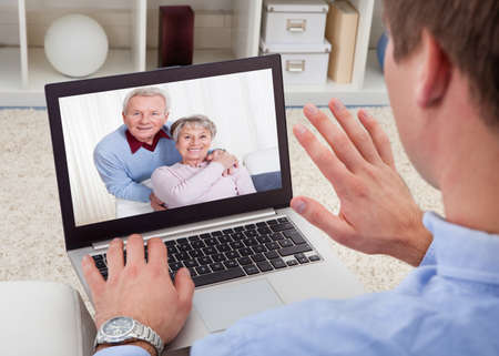 home video: Close-up Of A Man Video Chatting On Laptop With His Parents Stock Photo