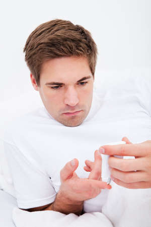 blood glucose: Young Man Examining Blood Sugar Level Of His Own Stock Photo
