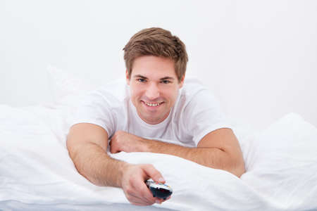 changing channel: Young Man Lying On Bed Changing Channel With Remote Control