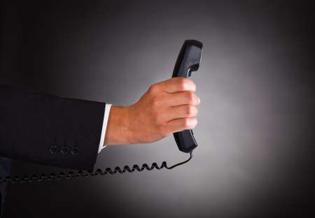Close-up Of Hand Holding Telephone Receiver Over Black Background photo