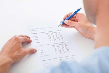 Close-up einer Person Ausfüllen Survey Form mit Stift Standard-Bild