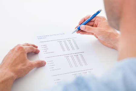 Close-up Of A Person Filling Survey Form With Pen photo