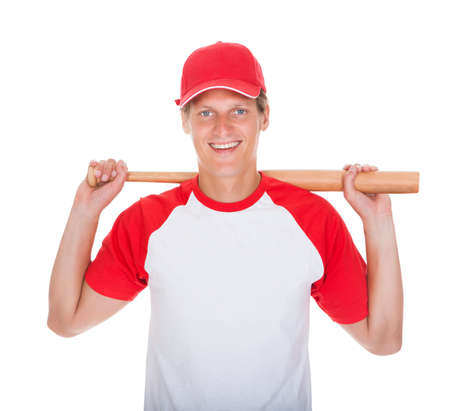 Portrait Of Player Swinging With Baseball Bat Over White Background photo