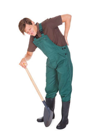 Male Gardener Suffering From Back Pain On White Background photo