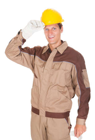 Portrait Of Happy Young Mechanic Wearing Yellow Hardhat On White Background photo