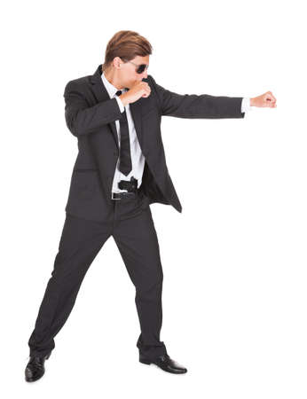 Young Man In Black Suit Punching On White Background photo