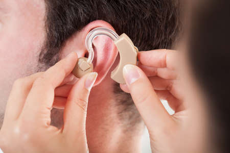 auditory: Close-up Of Hand Helping Young Man To Wear Hearing Aid
