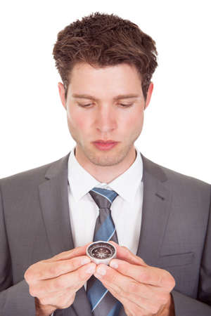Close-up Of Young Businessman Looking At Compass photo