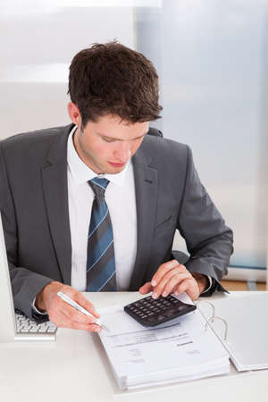 male facial: Happy Young Businessman Calculating Bills At Desk