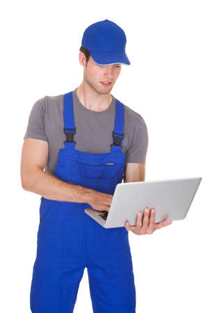 Portrait Of Happy Mechanic Holding Laptop On White Background photo