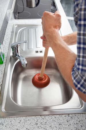 Closeup Of Man Using Plunger In Kitchen Sink Stock Photo