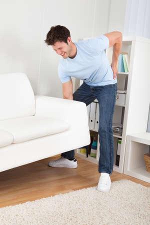 Hombre hermoso joven con dolor de espalda de elevación Couch Foto de archivo