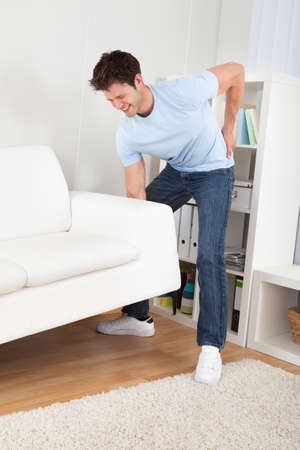 Young Handsome Man With Backache Lifting Couch photo